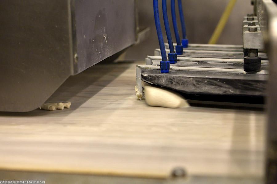 А вот здесь начинает собственный путь будущая булка.  Из одной машинки выпадает комок теста определенного размера...